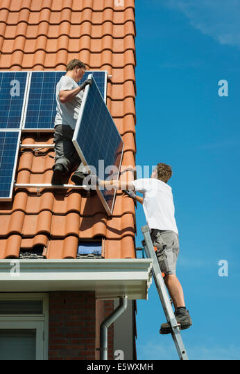 Workers installing solar panels on roof of new home, Netherlands - Stock Image