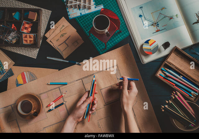 Designer workplace with creative tools and house blueprints - Stock Image