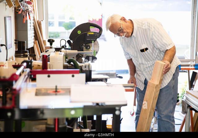 Senior man checking woodblock in carpentry workshop - Stock Image