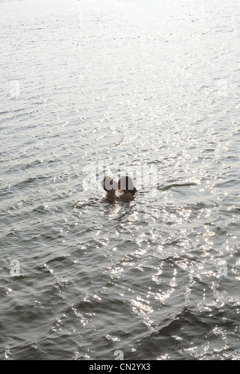 Couple kissing in the ocean - Stock-Bilder