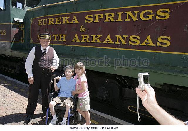 Arkansas Eureka Springs Eureka Springs and North Arkansas Railway conductor man girl boy disabled wheelchair passenger - Stock Image