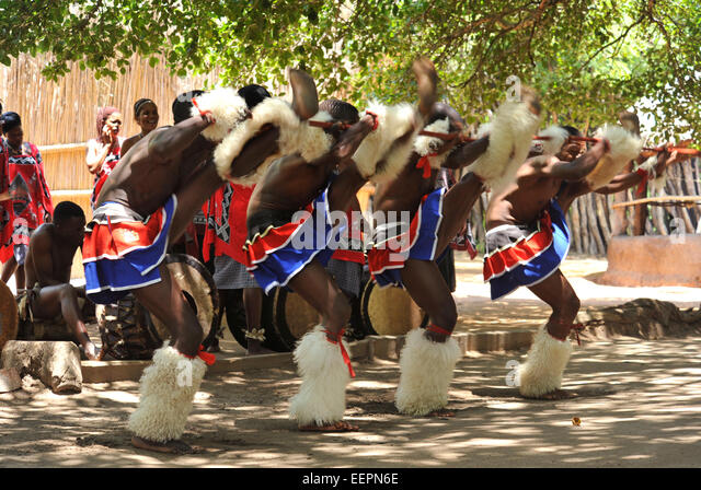 Group of Swazi male traditional dancers perform synchronised high kick during show for tourists at Matsamo Swaziland - Stock-Bilder