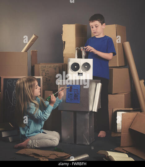 Children are building a metal robot from cardboard boxes with tools and books for an imagination, science or education - Stock Image