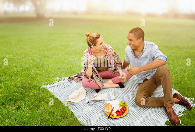 Mid adult couple having picnic in park - Stock Image