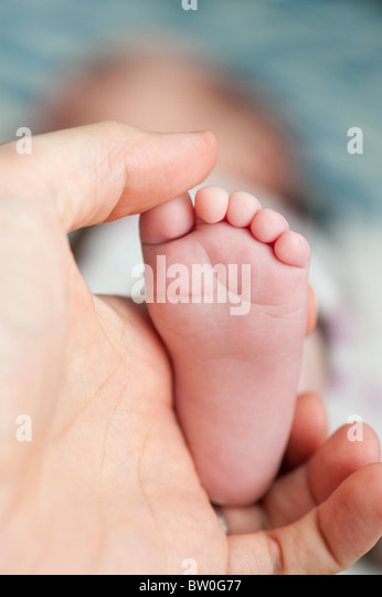 Father holding foot of baby girl - Stock Image