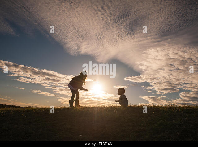 Silhouette of a girl with a baby learning to walk - Stock Image