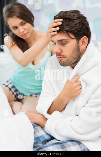 Young woman checking man's temperature on bed - Stock Image