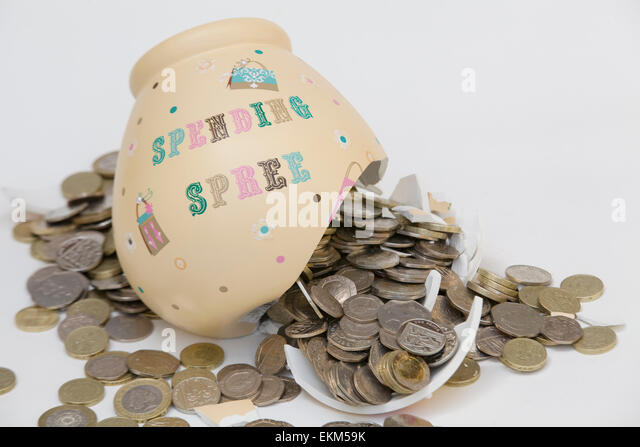 Smashed Money box with Coins pouring out of it on a white background - Stock Image
