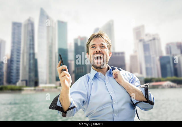 Ecstatic businessman holding smartphone on city waterfront - Stock Image