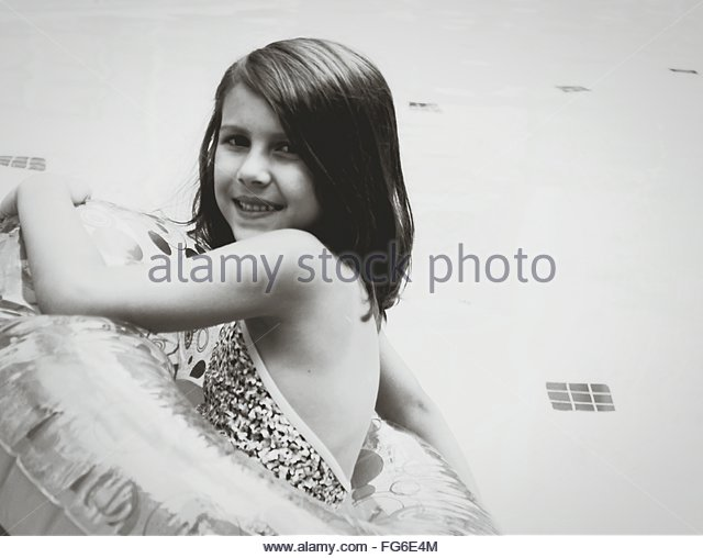 Portrait Of Smiling Girl In Float At Swimming Pool - Stock Image