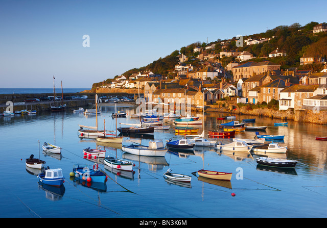 The first light of dawn catching the cottages along the waterfront, overlooking the picturesque Cornish Harbour - Stock Image