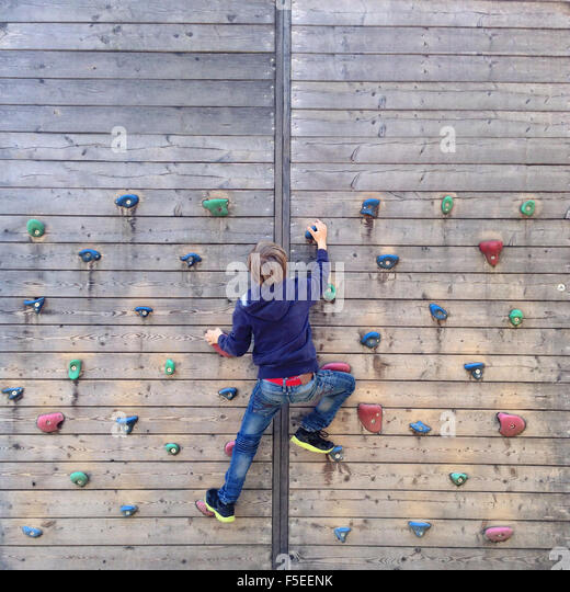 Boy climbing on climbing wall - Stock Image