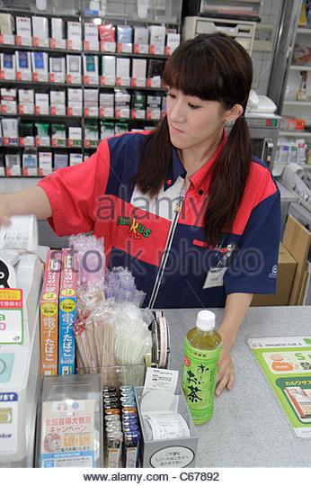 Tokyo Japan Ikebukuro business Circle K Sunkus Convenience Store Asian woman uniform cashier check-out bottle green - Stock Image