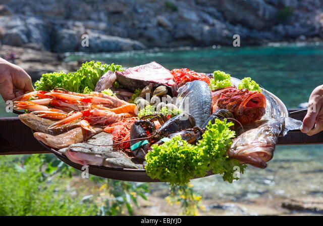 Hand of waitress and waiter with fresh seafood platter, Mallorca, Spain - Stock Image