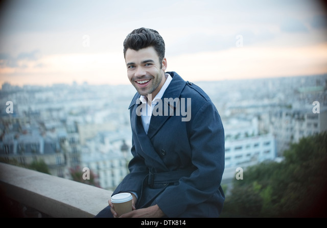 Businessman drinking coffee on ledge overlooking Paris, France - Stock Image