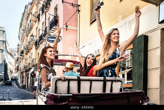Three young women in open back seat of Italian taxi, Cagliari, Sardinia, Italy - Stock Image