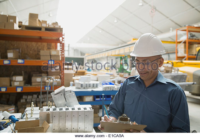 Worker with clipboard in manufacturing plant - Stock Image