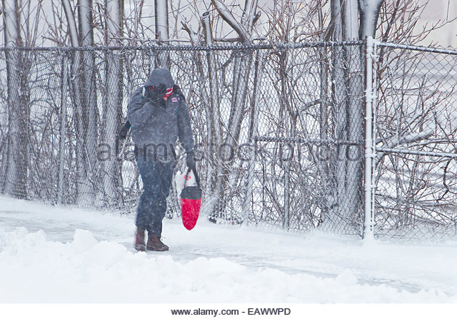 A man on a snow covered sidewalk battles the wind during the Blizzard of 2013. - Stock Image