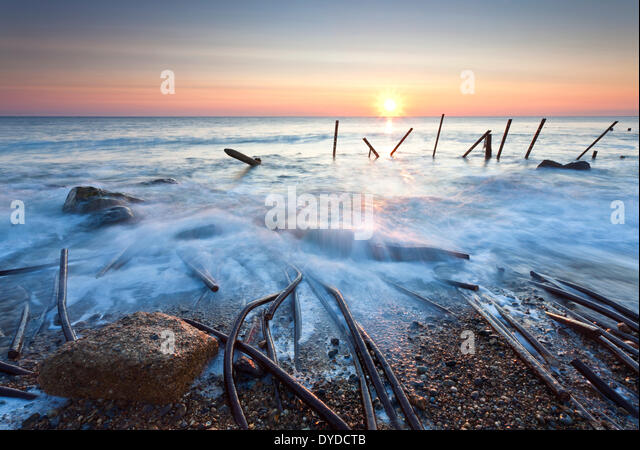 Happisburgh beach and the derelict sea defences at first light on the Norfolk coast. - Stock Image