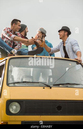 Group of friends drinking beer on pick-up truck - Stock Image