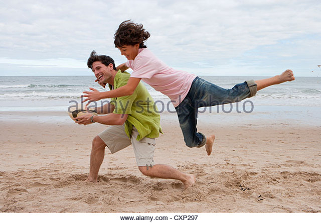 Son Performing Flying Mid Air Rugby Tackle On Father - Stock Image