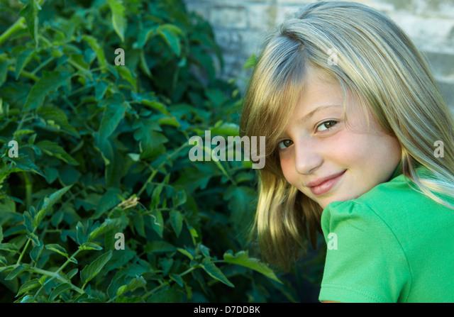 7 year old girl looking over her shoulder - Stock Image