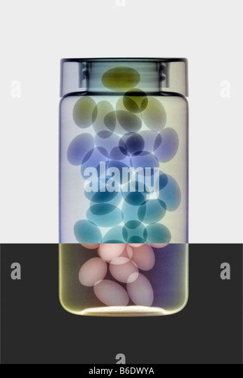 Oil capsules and in a bottle, coloured X-ray. - Stock-Bilder