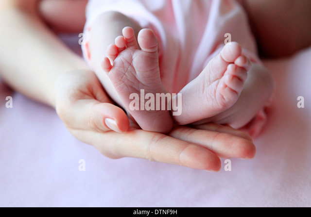 Parent hand hold baby girl legs - Stock Image