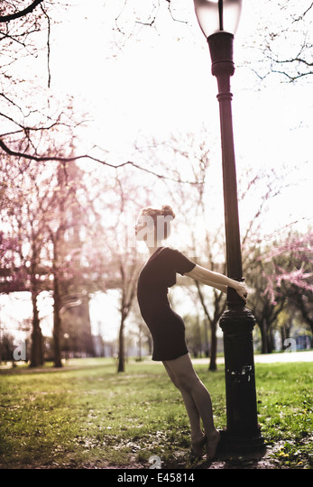 Modern dancer striking a pose in a urban park - Stock-Bilder