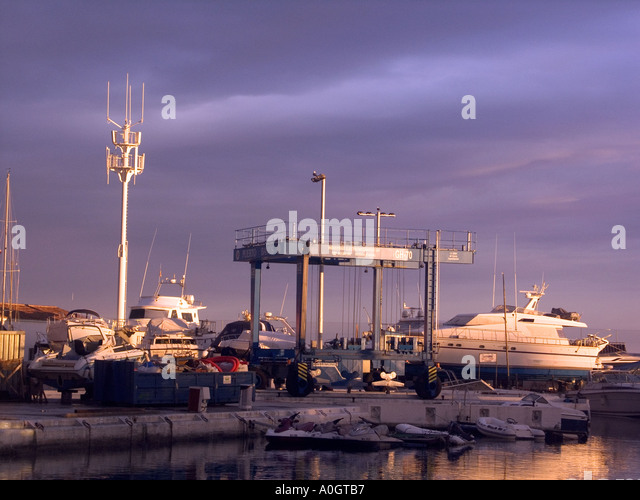 Puerto Banus, Costa del Sol , Spain, dusk evening light boatyard boatyards sunset sunsets buildings playground of - Stock Image