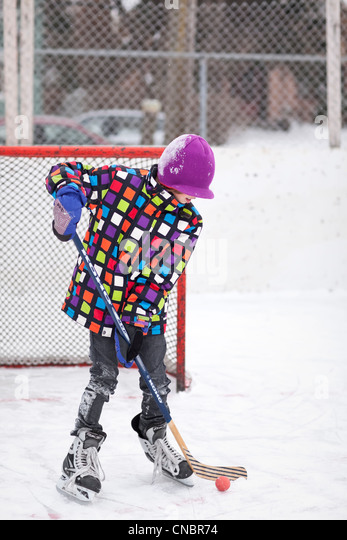 Boy playing ice hockey, outdoor rink, Winnipeg, Manitoba, Canada - Stock Image