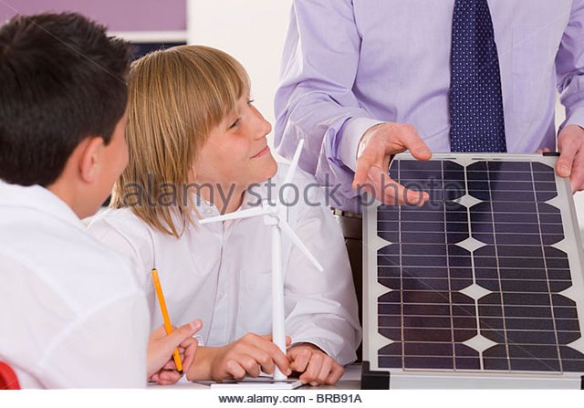 Students listening to teacher explaining solar panel and wind turbines in classroom - Stock Image