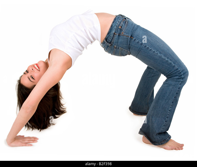 A young beautiful brunette is in bridge pose - Stock Image