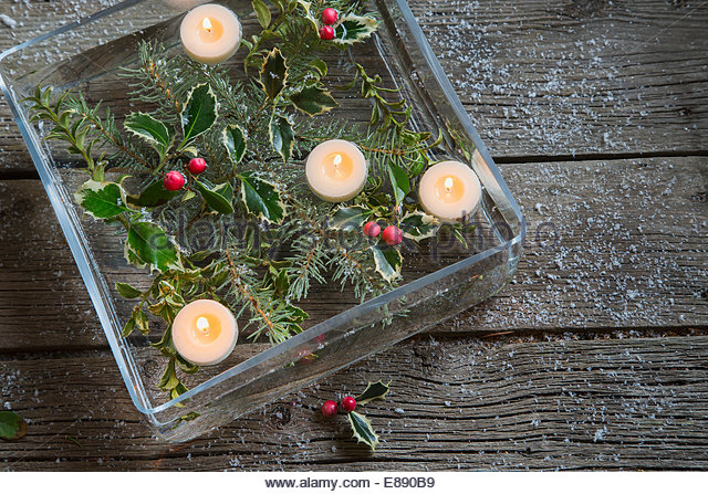 Floating candles and Christmas holly in square vase - Stock Image