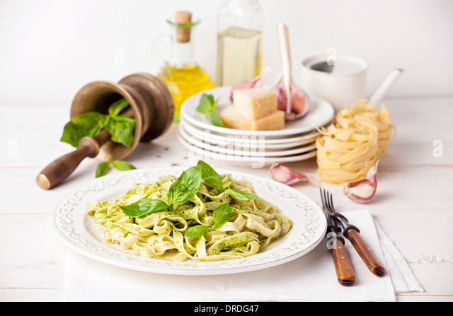 Pasta with pesto on white plate - Stock Image