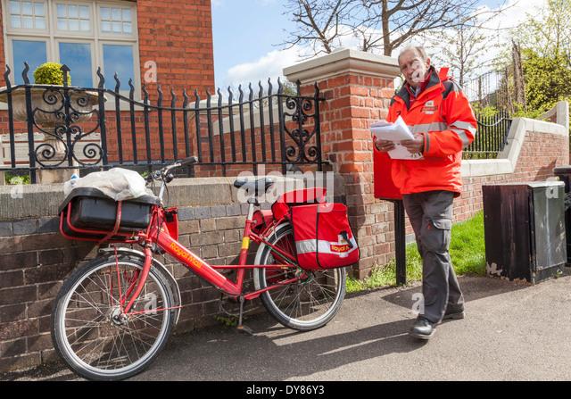 Village postman delivering post, Plumtree, Nottinghamshire, England, UK - Stock Image