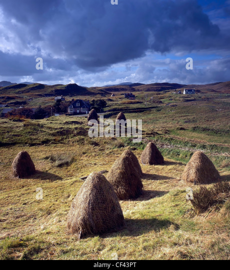 View over traditional, hand gathered hay bales towards the scattered community of Lacasaidh on the Isle of Lewis. - Stock Image