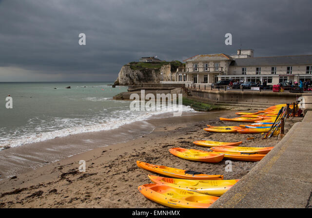 Bright orange canoes line up along the beach before a storm on the Isle of Wight - Stock Image