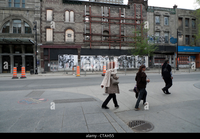 People walking past road works and closed stores in a revitalization area on Boulevard Saint-Laurent Montreal Quebec - Stock Image