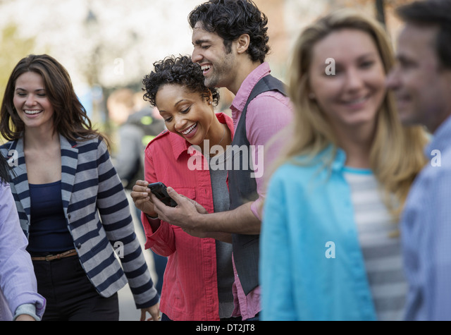 People outdoors in the city in spring time two looking at a cell phone screen and laughing - Stock Image