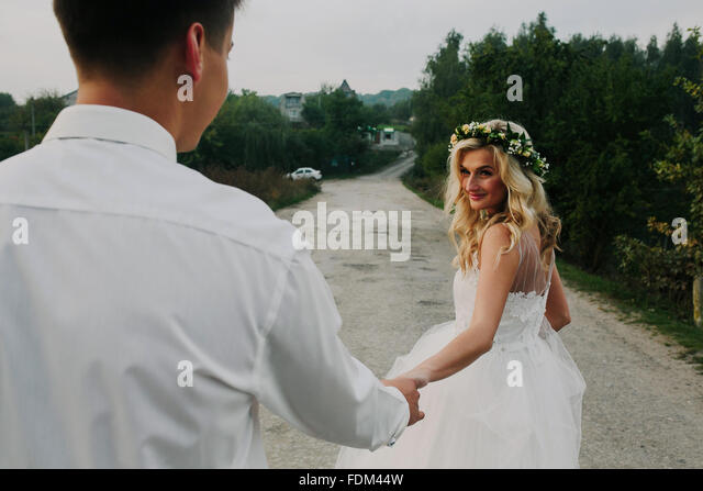 bride leads groom on the road - Stock-Bilder