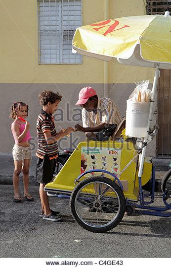 Santo Domingo Dominican Republic Ciudad Colonial Calle Padre Billini ice cream vendor cart Black Hispanic boy girl - Stock Image
