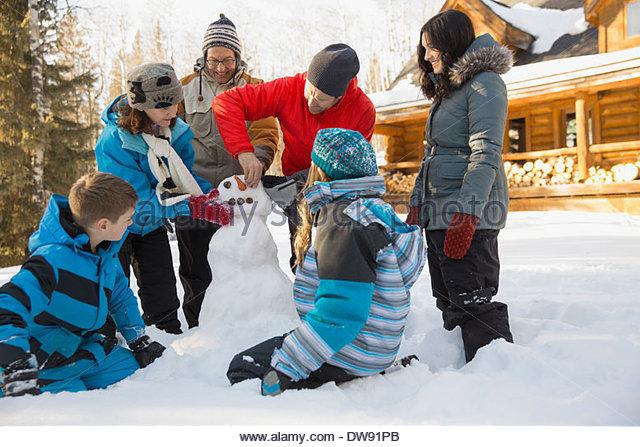 Three generation family building snowman - Stock Image