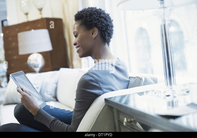 Woman relaxing at home with tablet - Stock Image