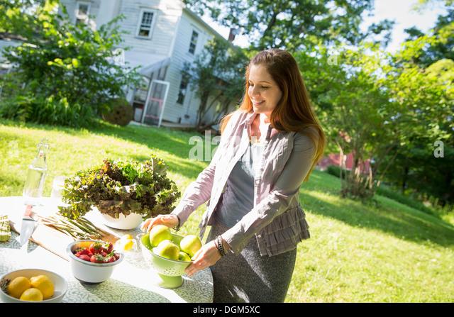 On farm woman in farmhouse garden preparing table fresh organic foods fresh vegetables salads bowls of fresh fruit - Stock Image