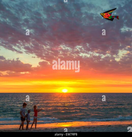 Three children flying a kite on beach at sunset, Hillarys, Joondalup, Australia - Stock Image