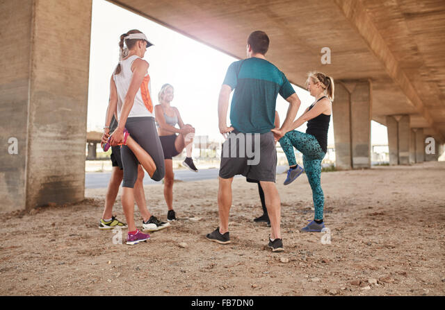 Group of healthy people stretching under a city bridge. Young men and woman taking a break from outdoor training. - Stock-Bilder
