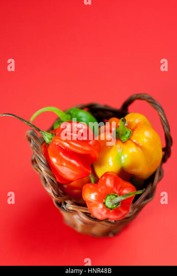 Small basket filled with mini hot peppers - Stock Image