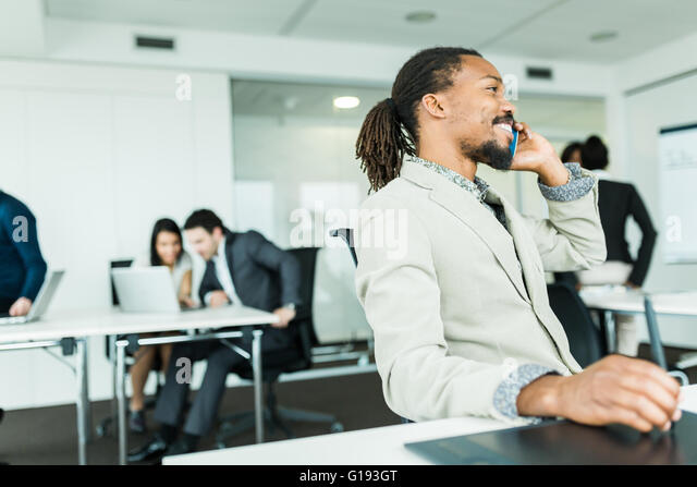 Black handsome graphics designer  with dreadlocks using digitizer in a well lit, tidy office environment and talking - Stock Image