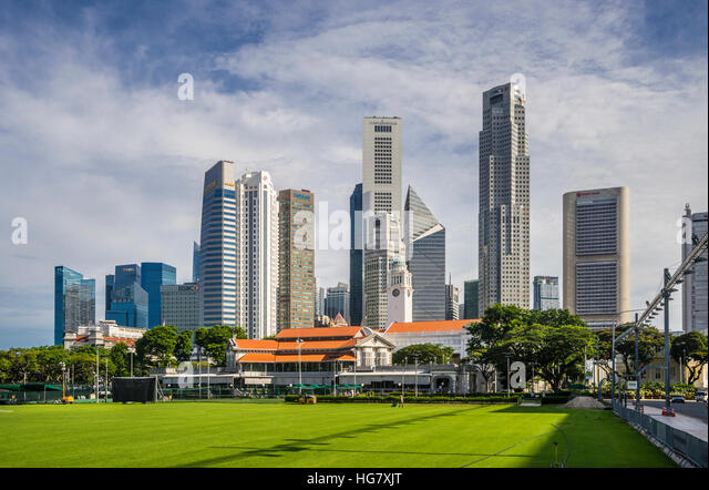 view of the Singapore skyline across the Padang open playing field with Singapore Recreation Club building - Stock Image